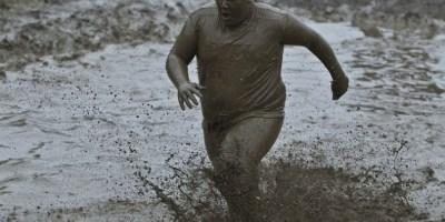 Gordo corriendo en el barro